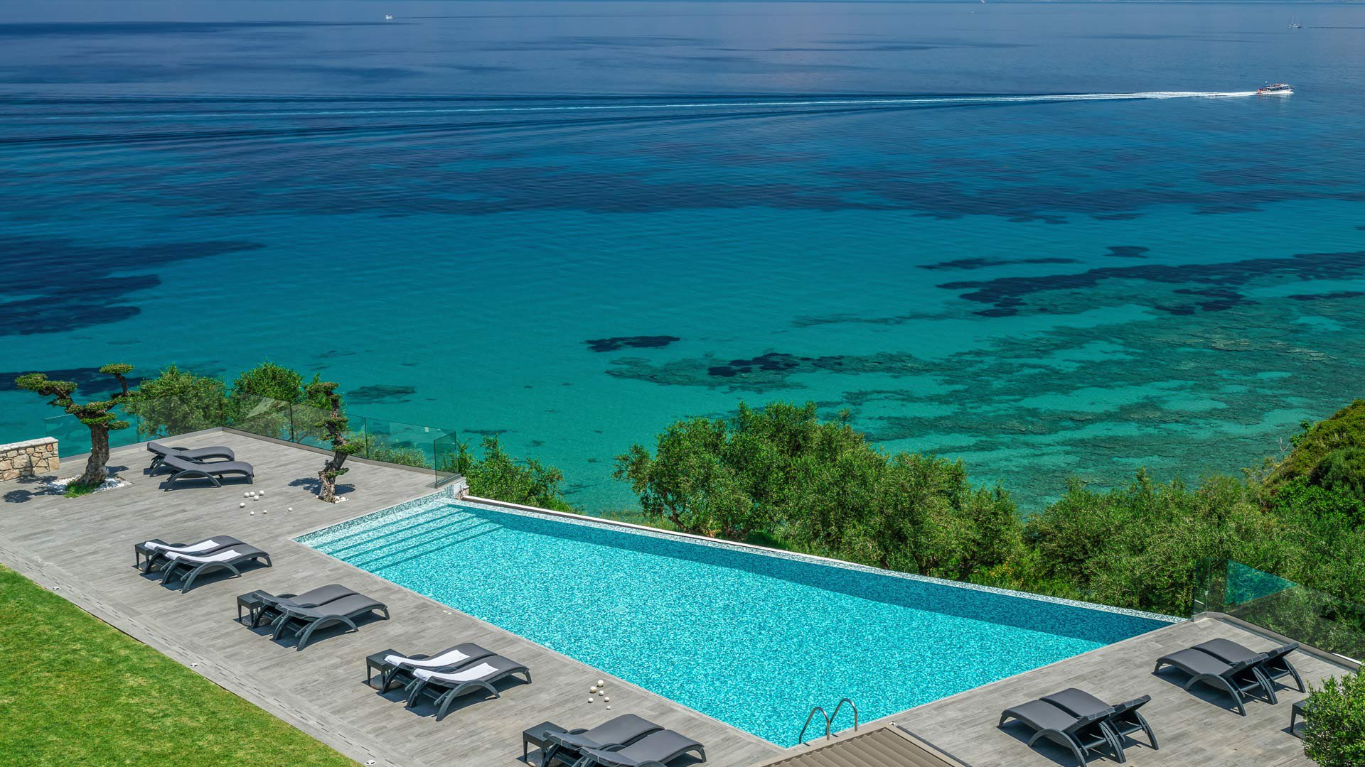 The sunbeds and the infinity pool that's merging with the Ionian Sea at Kymothoe Elite Suites in Zakynthos